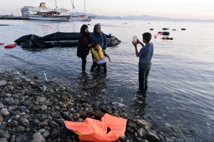 Syrian migrants take a picture after their safe arrival  on an overcrowded dinghy to the coast of the southeastern Greek island of Kos from Turkey, on August 15, 2015. A ferry boat has been sent by the Greek government to the resort of Kos to speed up the registration process of hundreds of Syrian refugees, docked on August 14 afternoon at the harbour. The Eleftherios Venizelos will stay moored in Kos for some two weeks, during which time authorities will register newcomers to the island, which is already overflowing with refugees and migrants. AFP PHOTO /LOUISA GOULIAMAKI